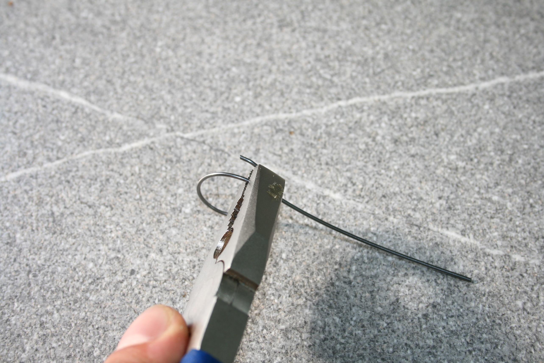 Federstahldraht mit Kombizange fixiert um überstehendes Ende radial zum Kreis zu biegen