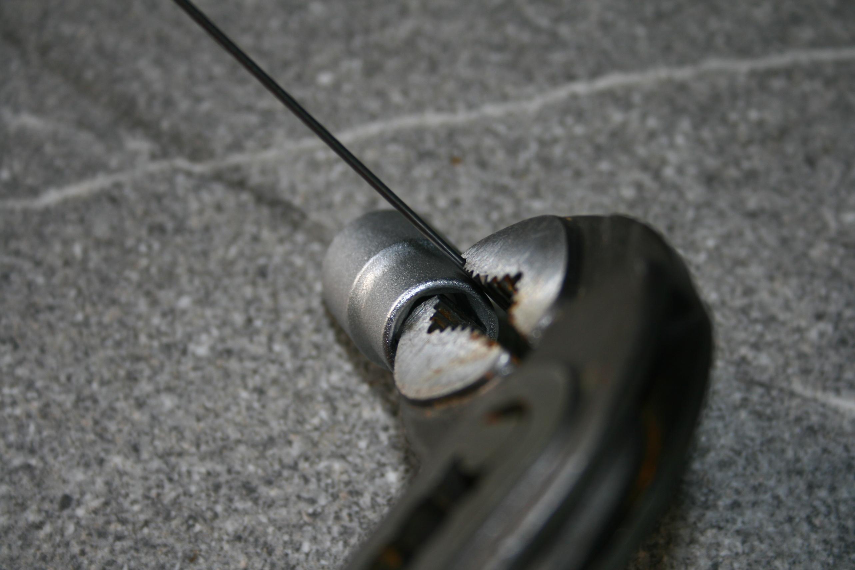Federstahldraht mit Wasserpumpenzange an Stecknuss festgehalten (Seite mit überstehendem Draht)